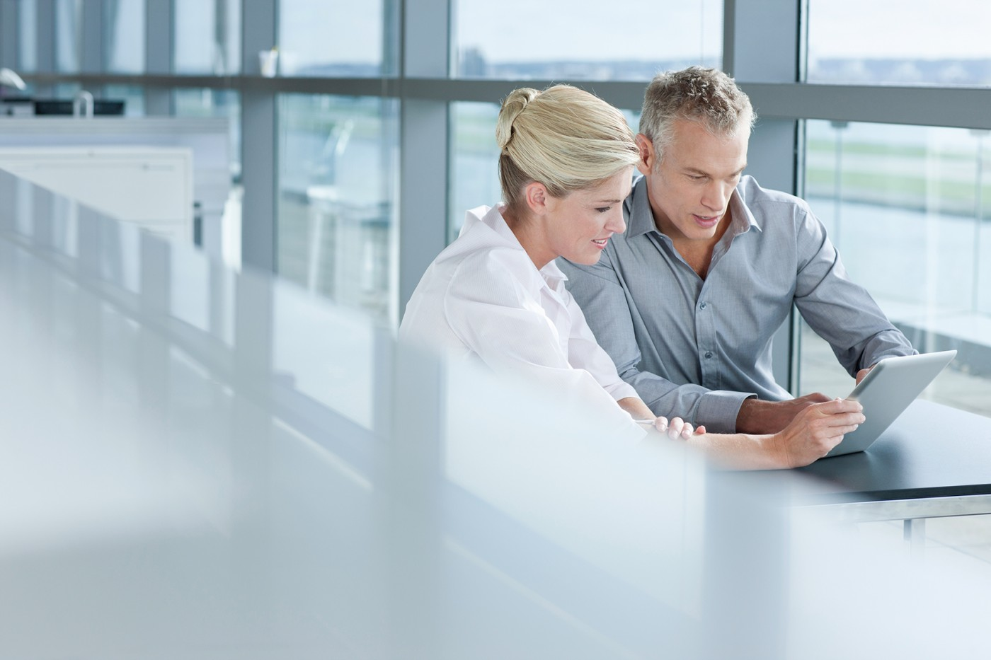 Businessman and businesswoman using digital tablet at office window